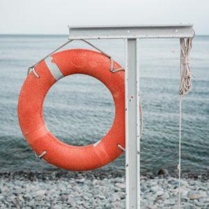 orange lifebuoy on the sea coast